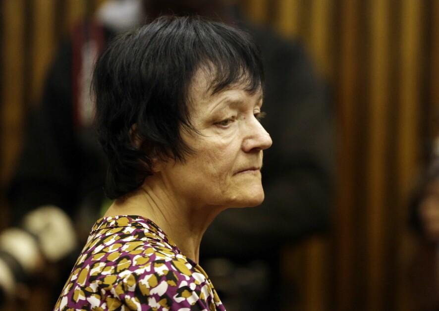 En äldre kvinna med kort svart hår ser sammanbiten ut.