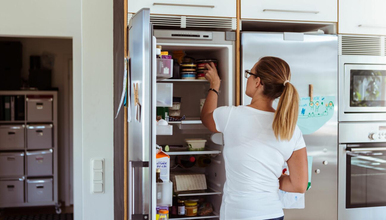 En kvinna står i ett kök och städar ur sin kylskåp. Kvinnan har vit t-shirt och en hästsvans.