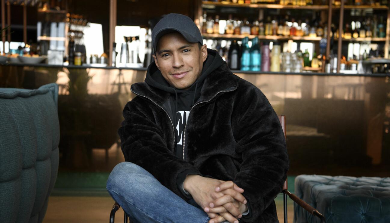 Jon Henrik sitter ner och tittar in i kameran. Han bär en svart jacka, blåa jeans och en mörk keps.
