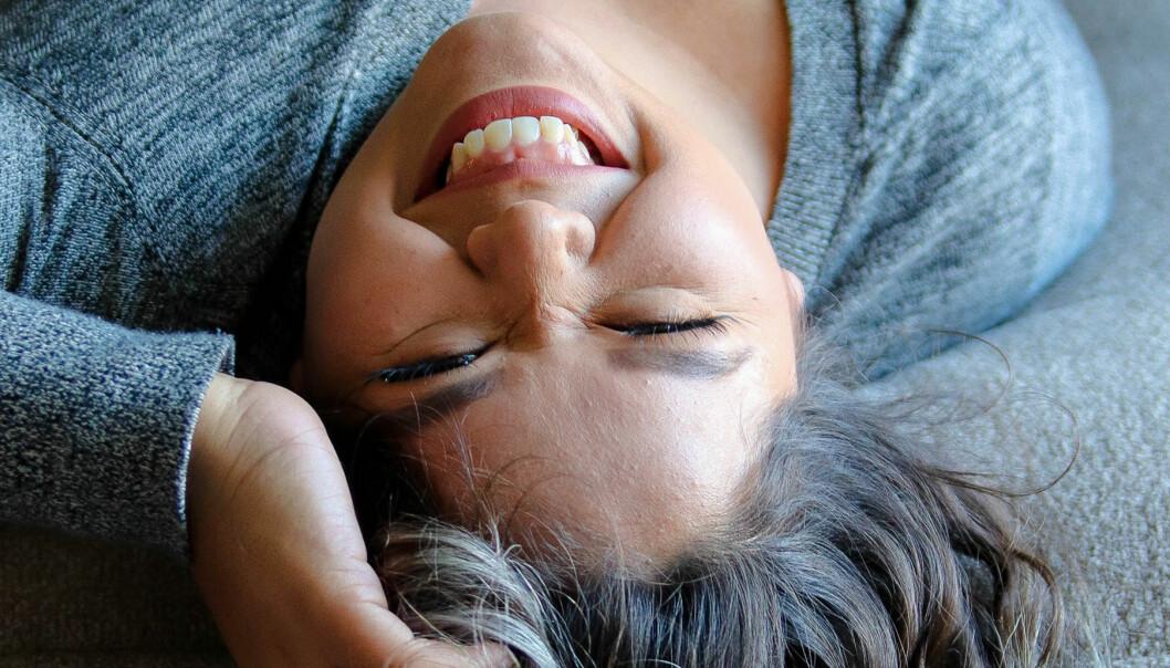 Kvinna ligger ner och skrattar mot kameran