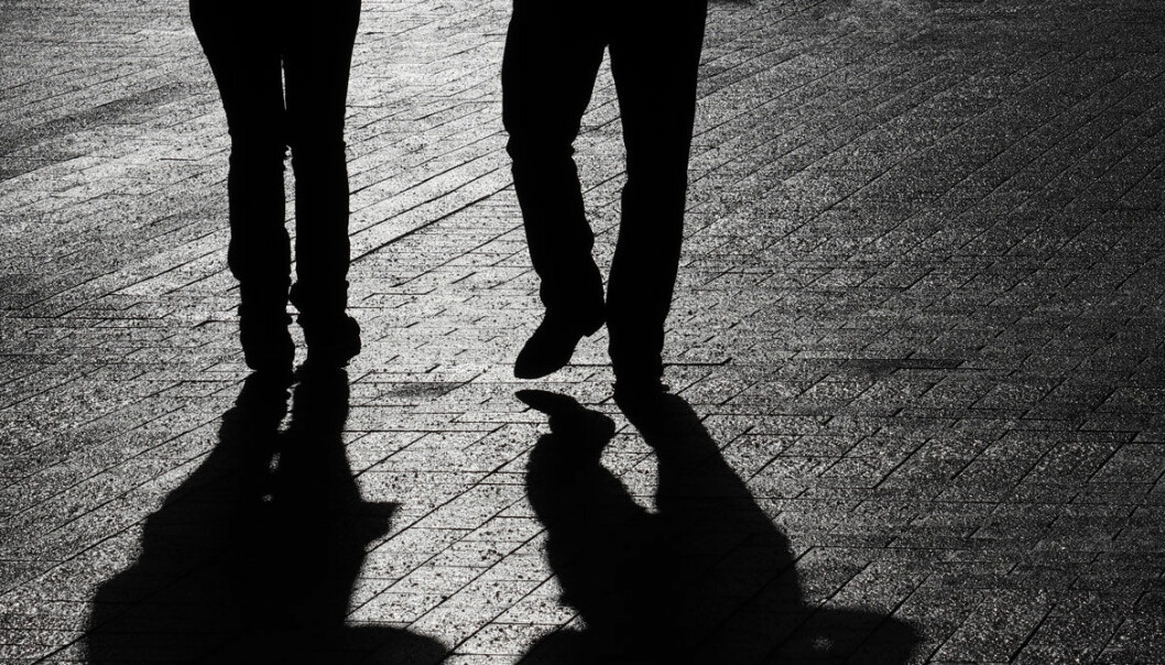 Siluetter av två personer som går på en trottoar