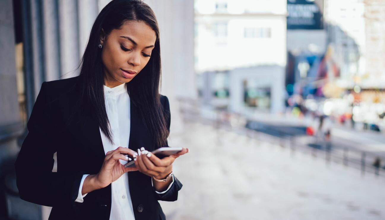 En afroamerikansk kvinna i kostym ser allvarligt ner i sin mobiltelefon.