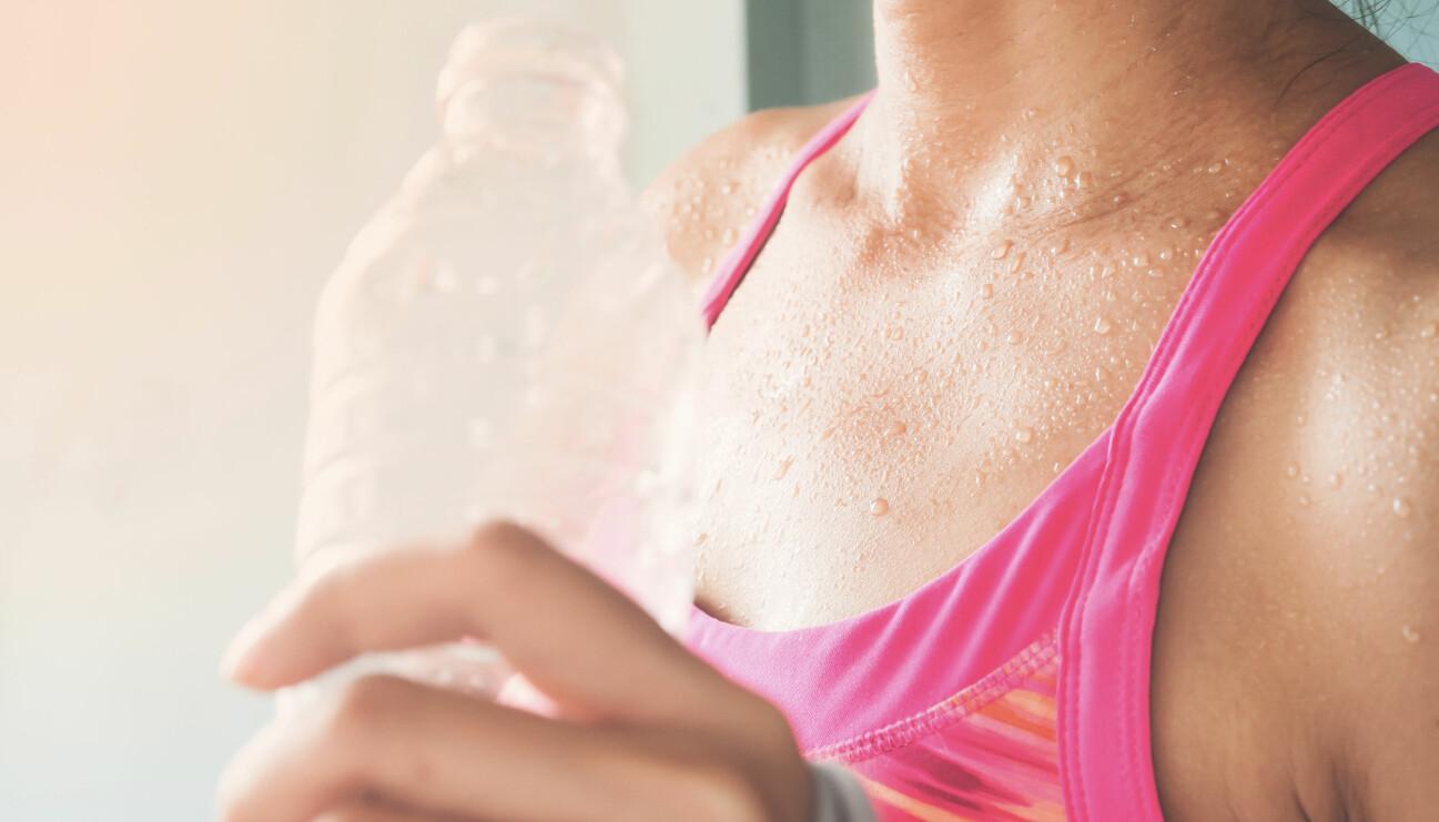 Svettig kvinna med vattenflaska
