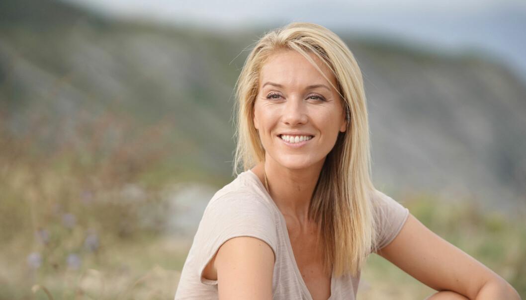 Kvinna i naturen ler