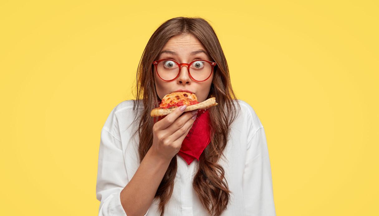 Kvinna äter pizza