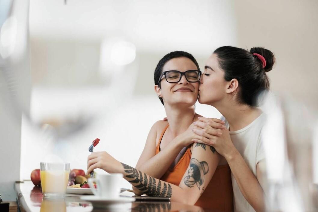Två kvinnor pussas vid ett bord