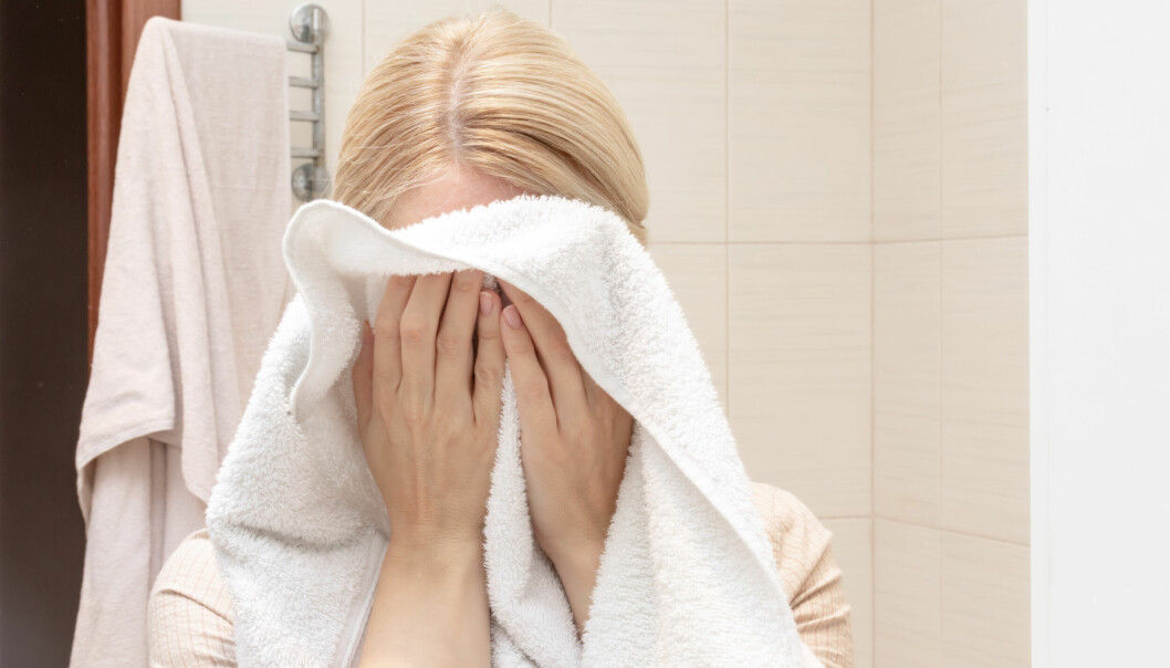 Kvinna torkar ansiktet på en handduk