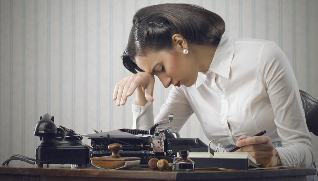 En kvinna i 1950-talsfrisyr ser trött ut vid ett skrivbord.