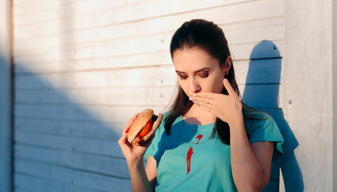 Kvinna spiller ketchup på sin tröja