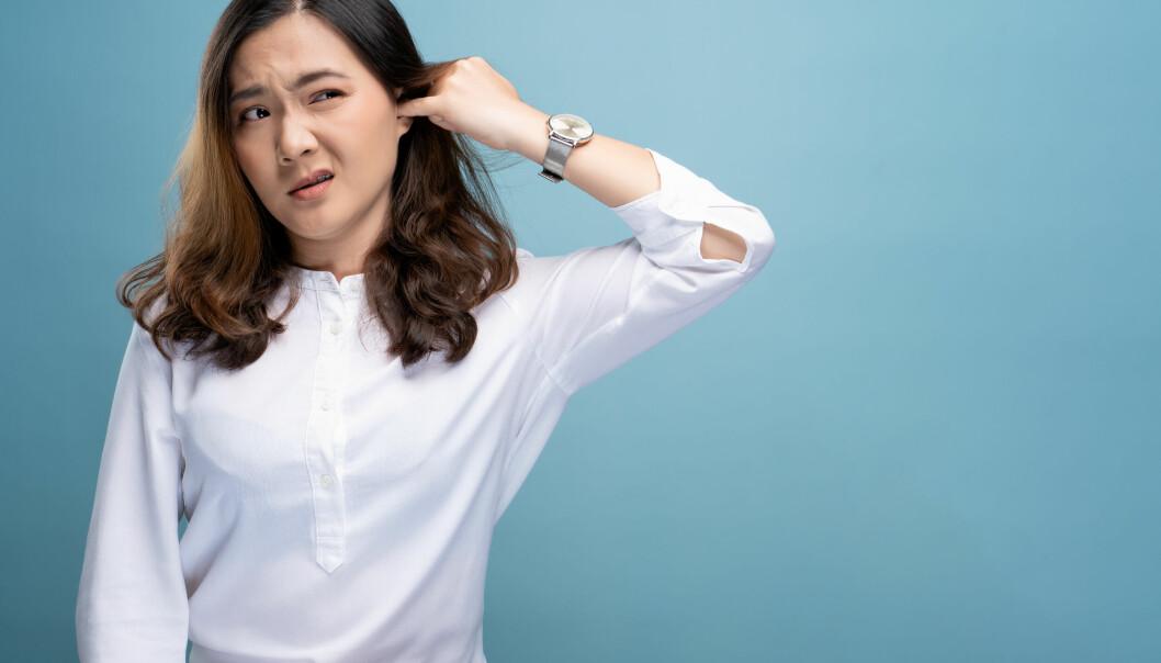Bild på en tjej i vit skjorta som stoppar fingret i örat och ser besvärad ut. Bilden har en ljusblå bakgrund.