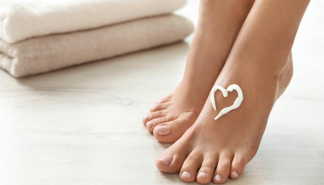 Ett par nakna fötter med kräm på i formen av ett hjärta.
