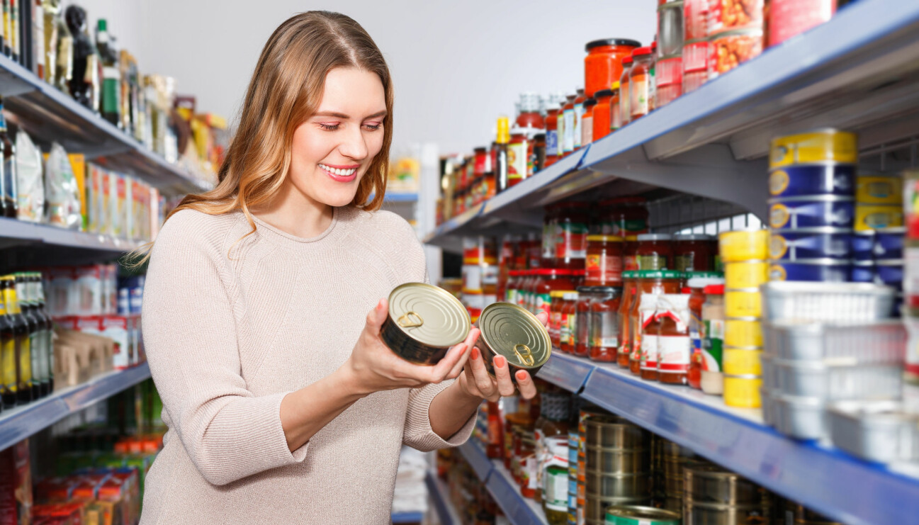 En kvinna i en matbutik ler och håller i två konservburkar.