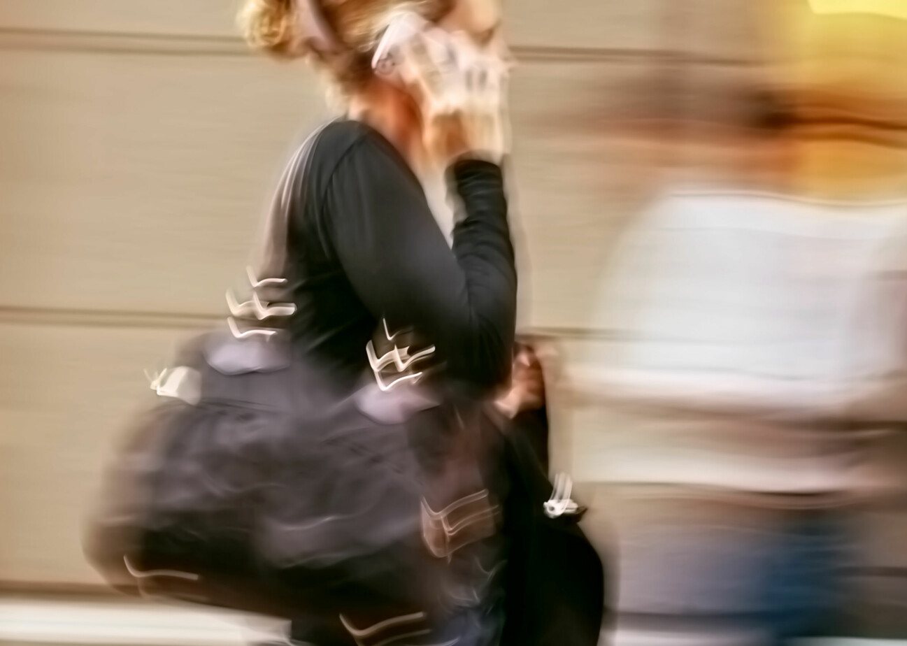 Kvinna talar i mobiltelefon och rör sig snabbt framåt.