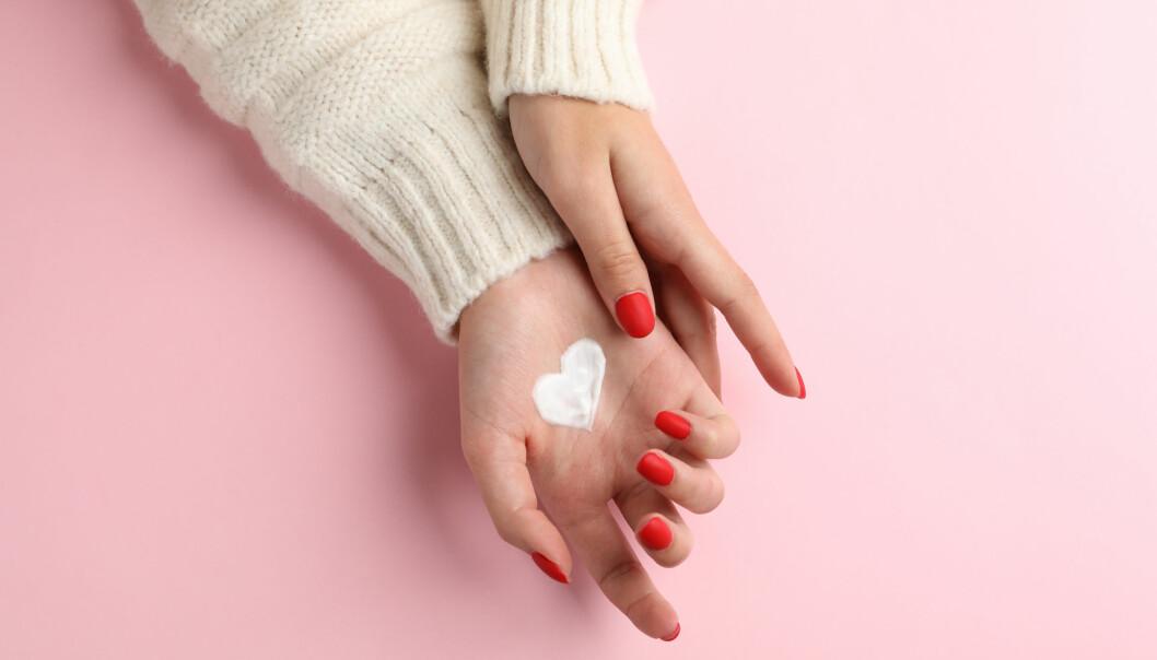 Kvinna med hudcreme i handen.