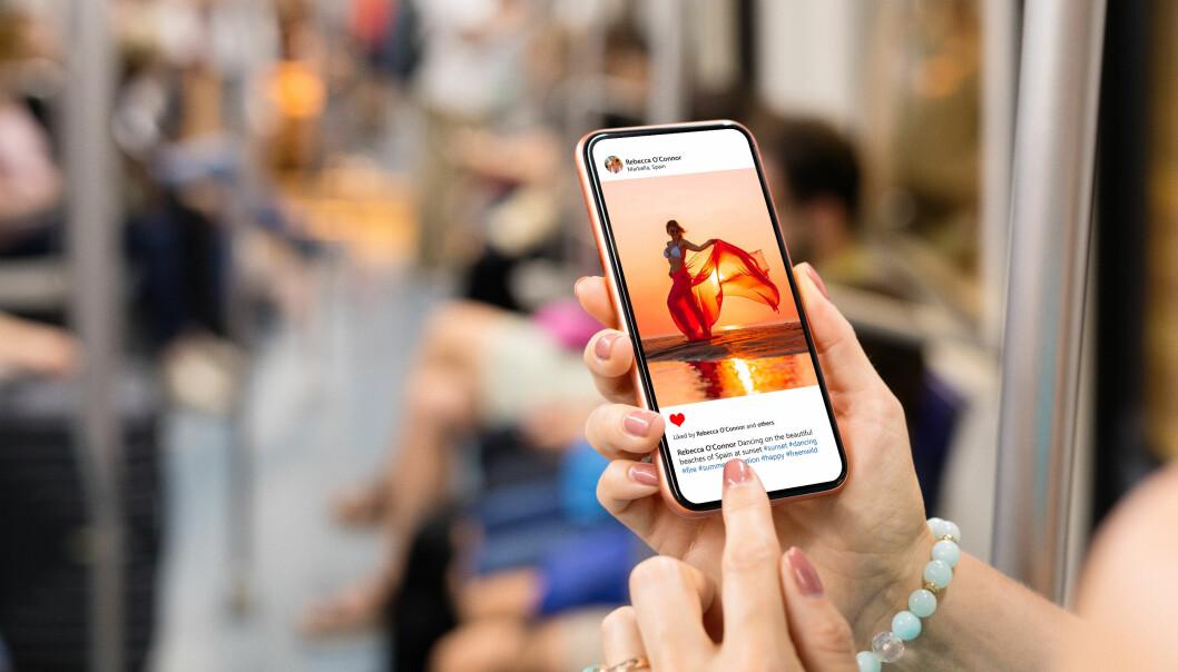 En kvinna håller upp sin telefon och skrollar på Instagram.