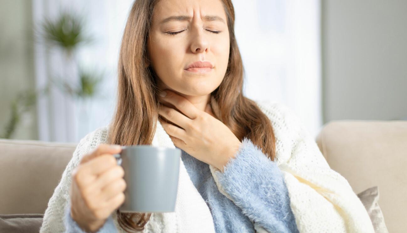 Kvinna med ont i halsen dricker te.