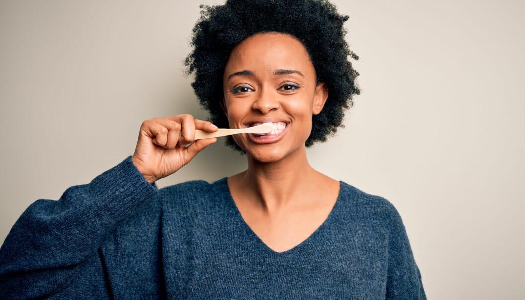 Glad kvinna borstar tänderna.