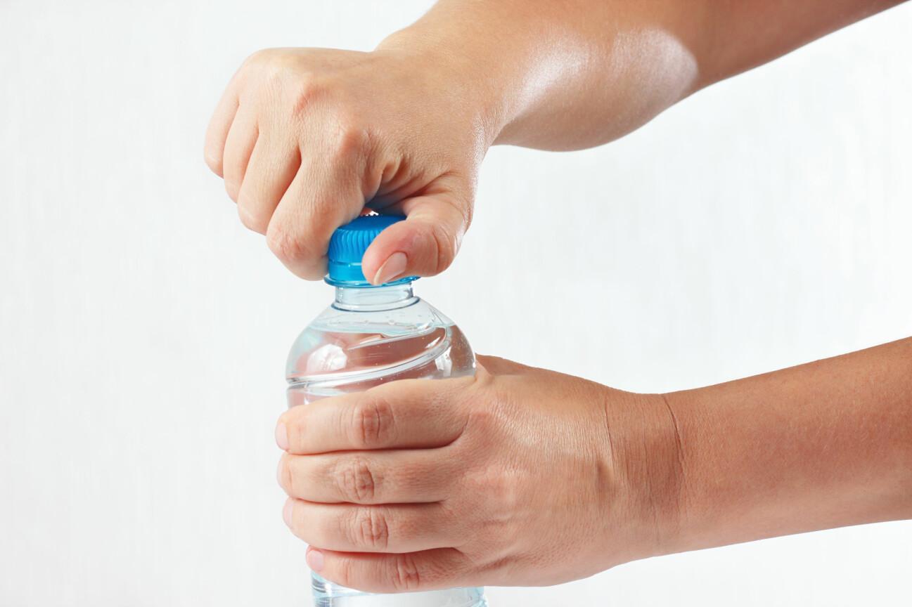 Kvinna skruvar av kork på flaska.