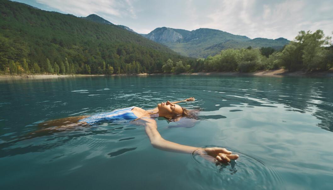 En kvinna flyter avslappnat på rygg i en skogssjö med blått vatten.