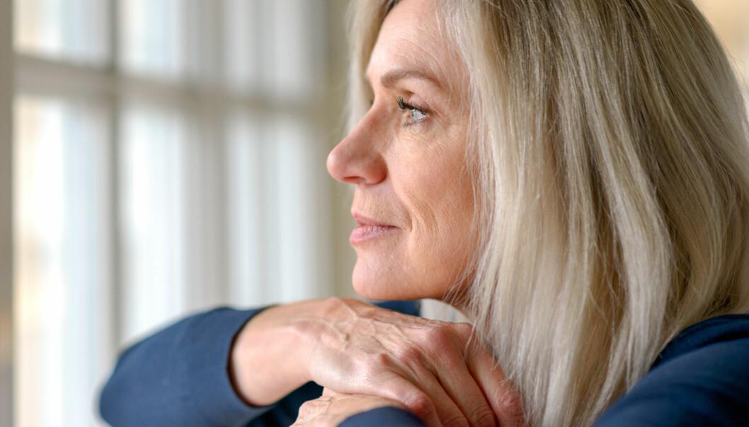 Kvinna sitter vid ett fönster och tittar ut