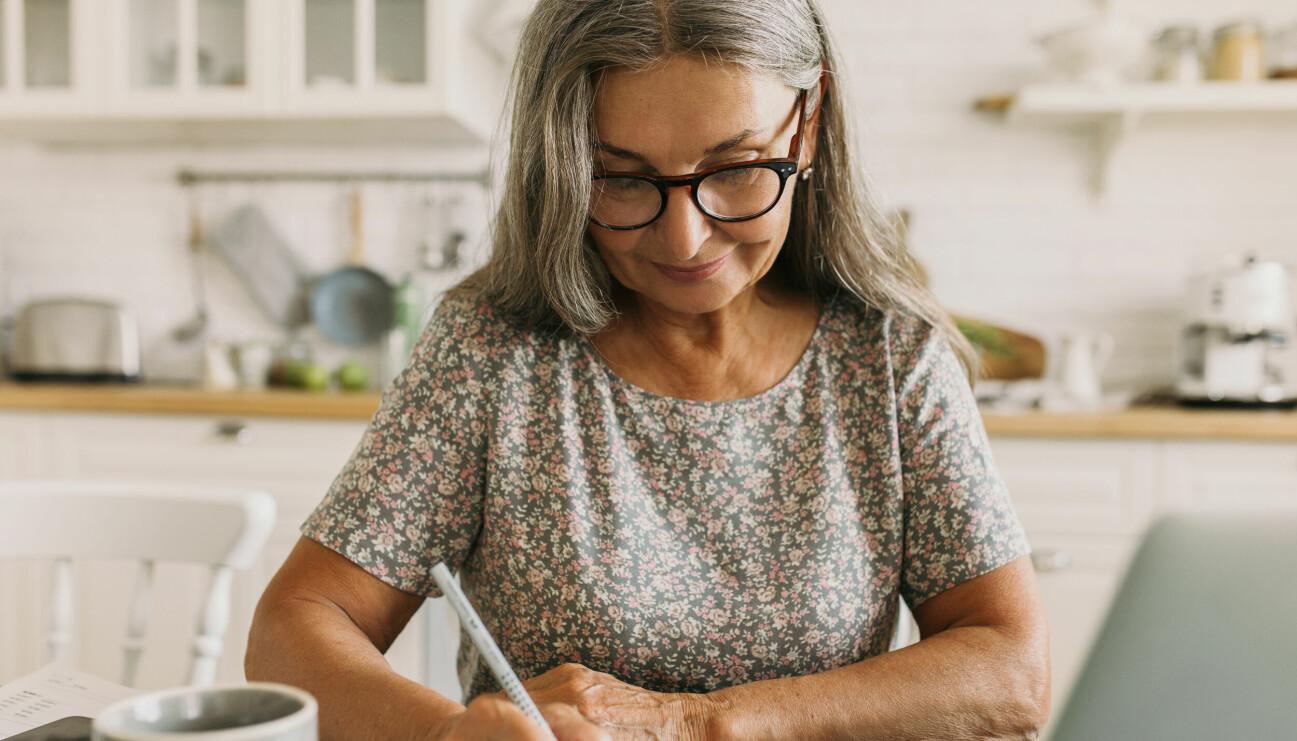 En kvinna i övre medelåldern skriver sitt testamente.