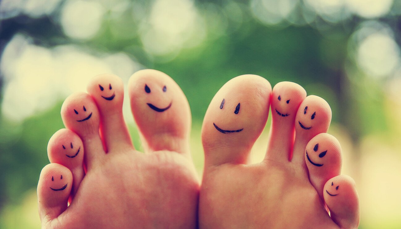 Ett par nakna fötter med glada gubbar ritade på undersidan av varje tå.