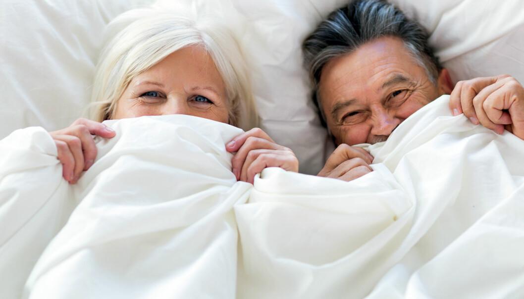 Kvinna och man kikar fram under ett vitt täcke.