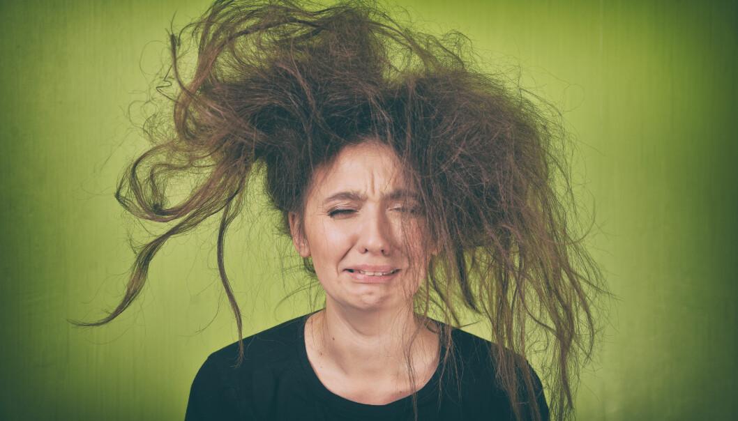 Upprörd kvinna med tovigt hår mot grön bakgrund.