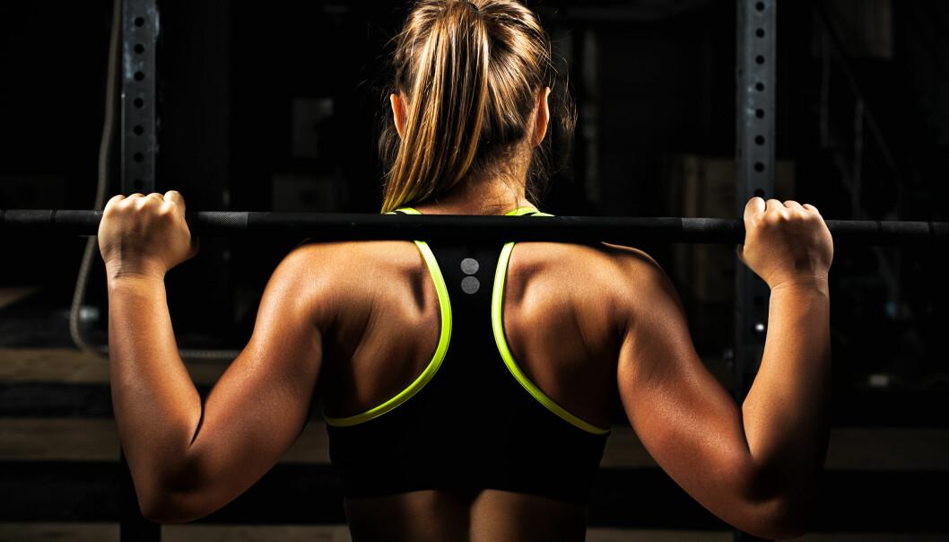 Kvinna i sport-bh syns bakifrån när hon styrketränar.