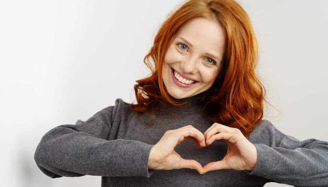Kvinna formar ett hjärta med händerna