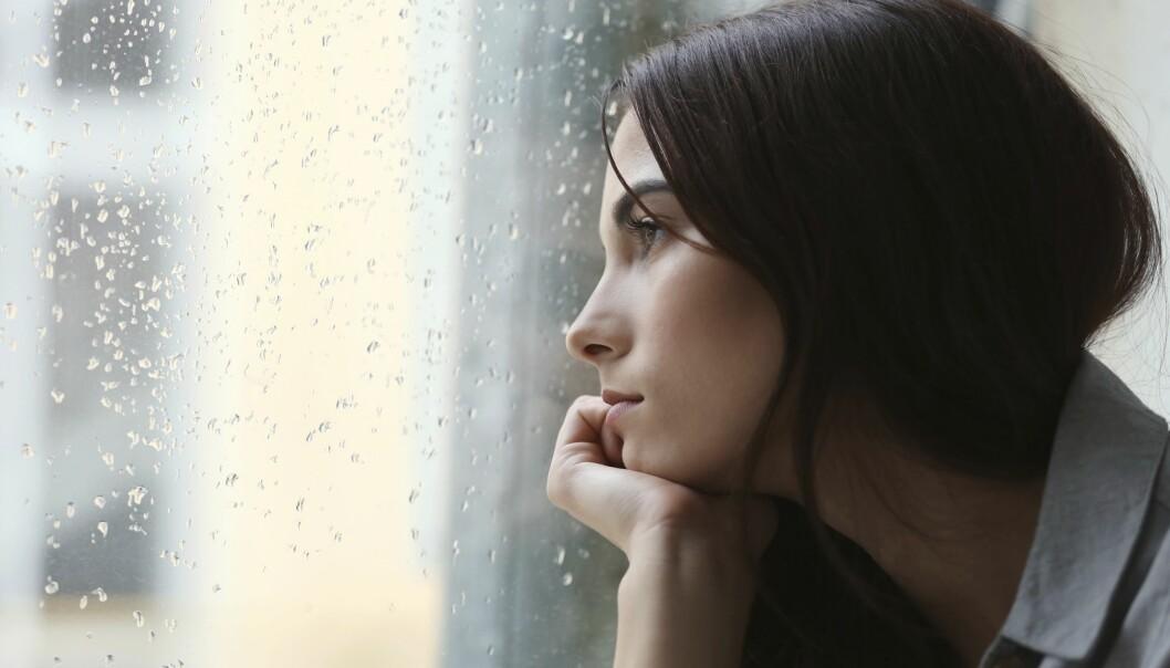 Ledsen ung kvinna tittar ut genom ett fönster