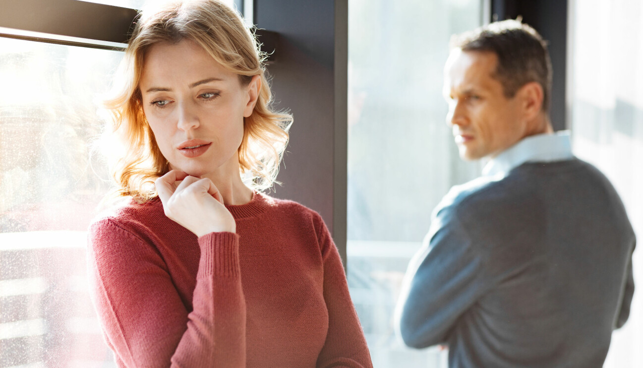 Ledsen kvinna står lutad mot ett fönster och tittar bort från en man som tittar mot henne med allvarligt ansiktuttryck.