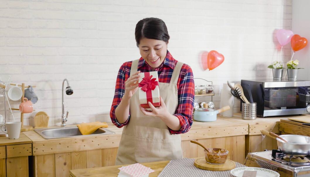 Kvinna i köket tittar nyfiket på en julklapp.