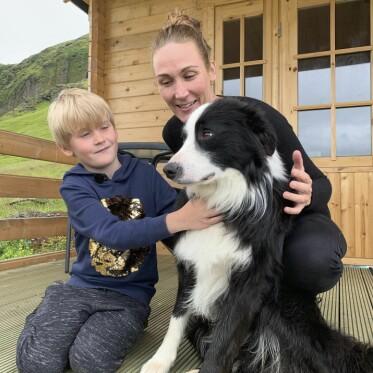 Silas och Christina sitter på golvet på en veranda och klappar en svartvit hund under ett besök på Island