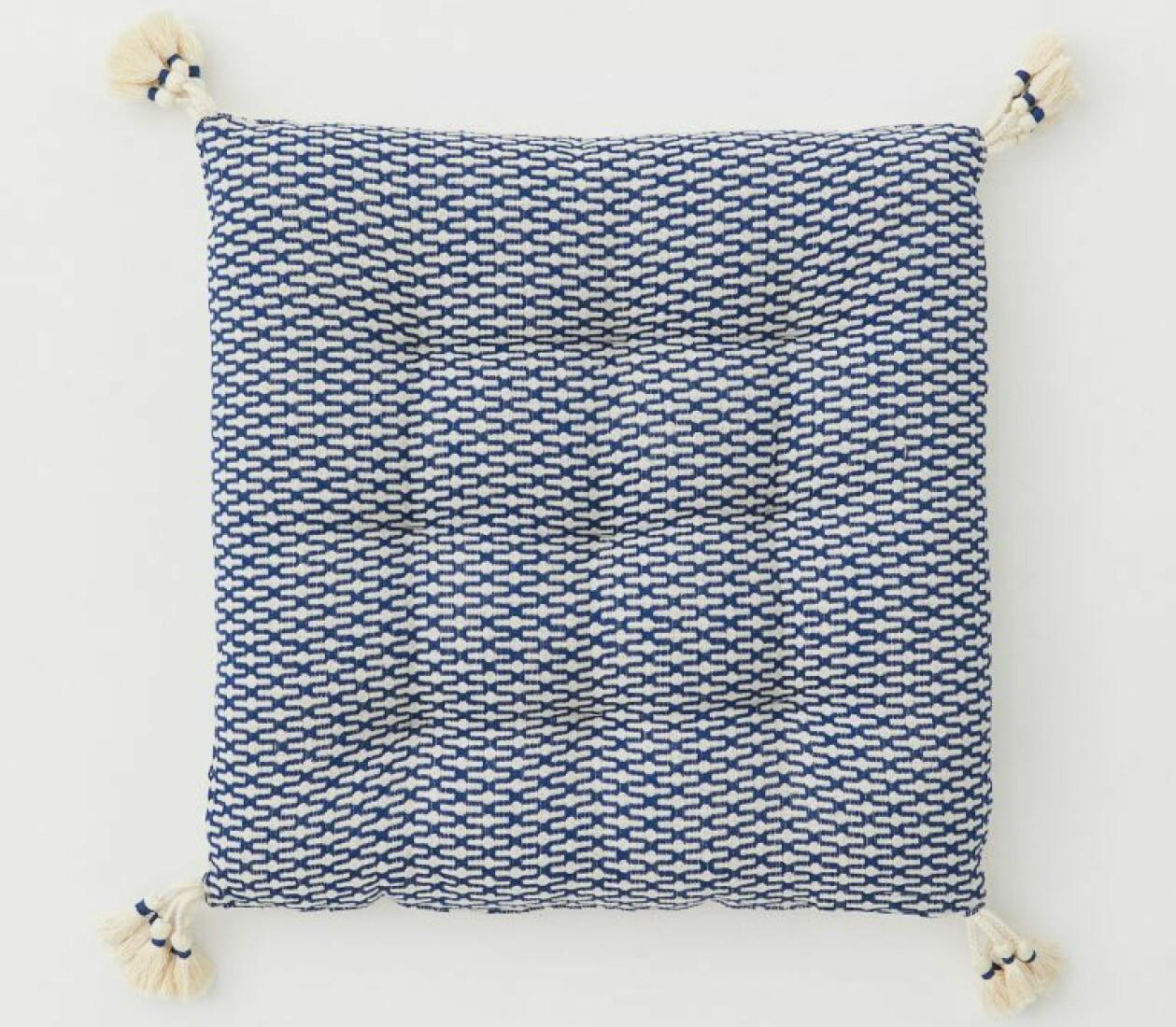 Sittdyna i blått och vitt med tofsar i hörnen, från H&M Home