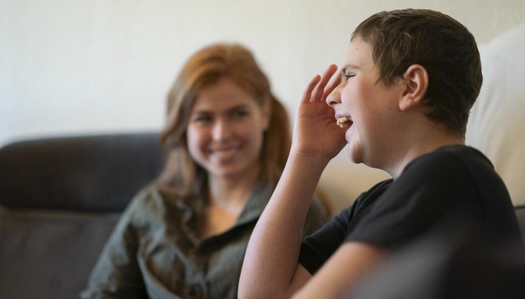 Sjuk pojke sitter med sin syster i en soffa.