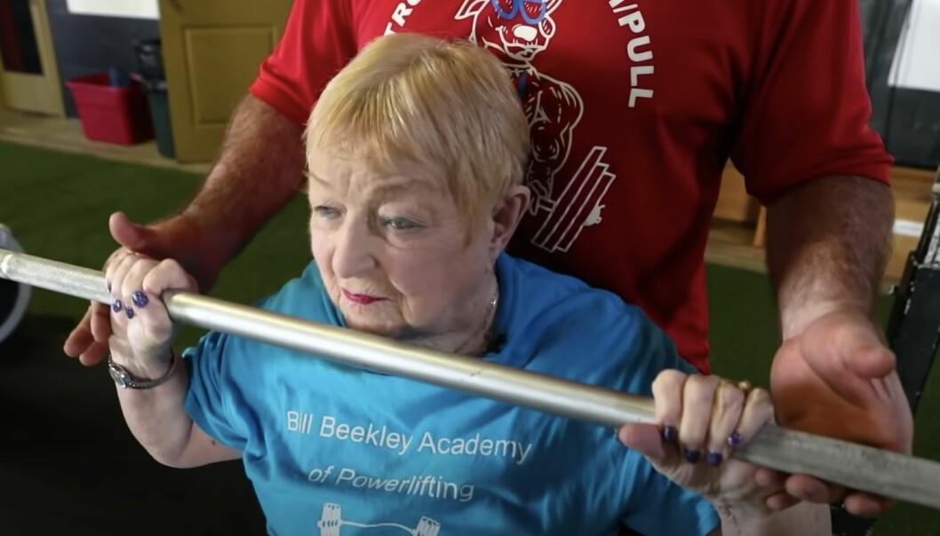 100-årig kvinna styrketränar.