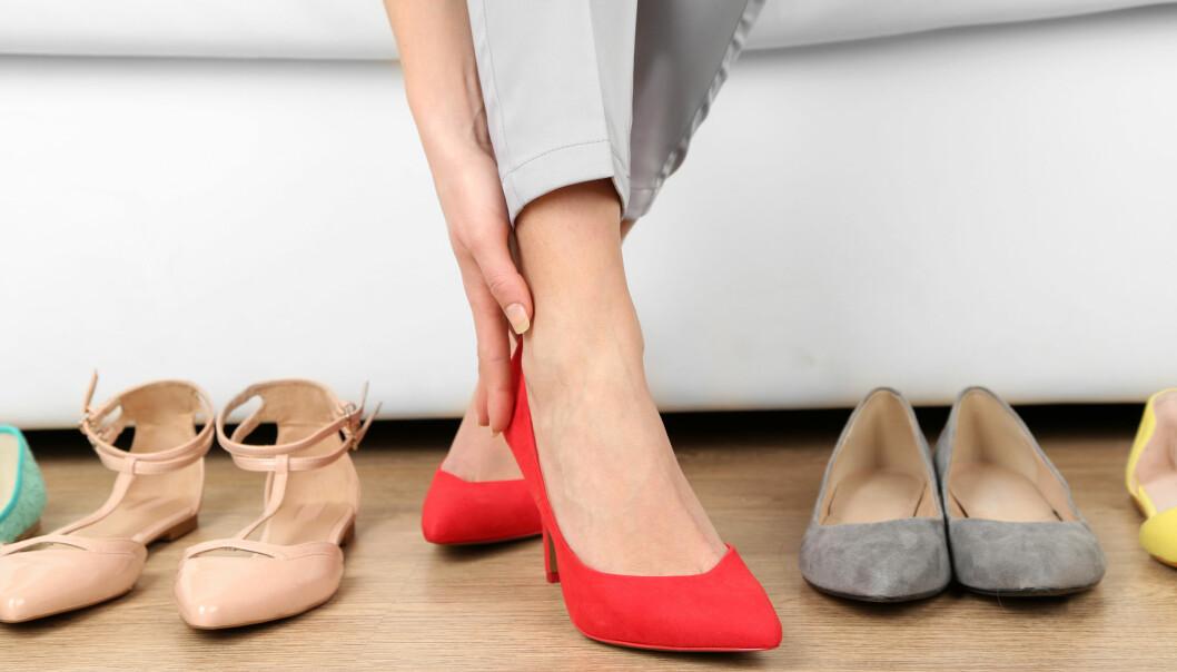 Kvinna tar på sig ett par skor.