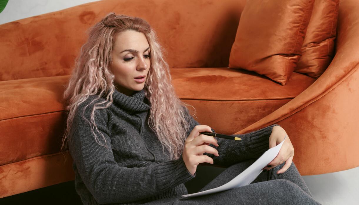 Ung kvinna med långt, blont, lätt rosa-slingat hår sitter på golvet framför kopparfärgad soffa och skriver en lista.