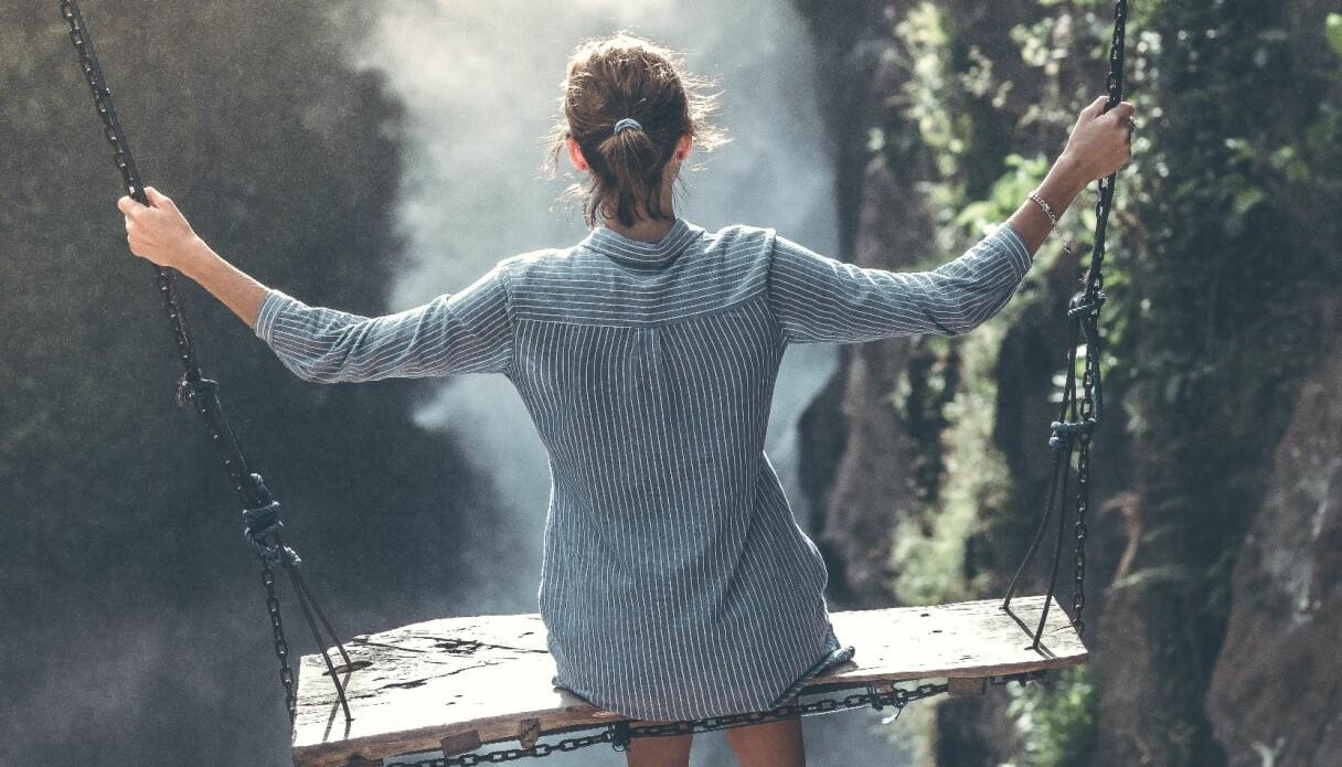 En äventyrlig kvinna som tydligt tillhör stjärntecknet skytten sitter på en gunga vid ett vattenfall.