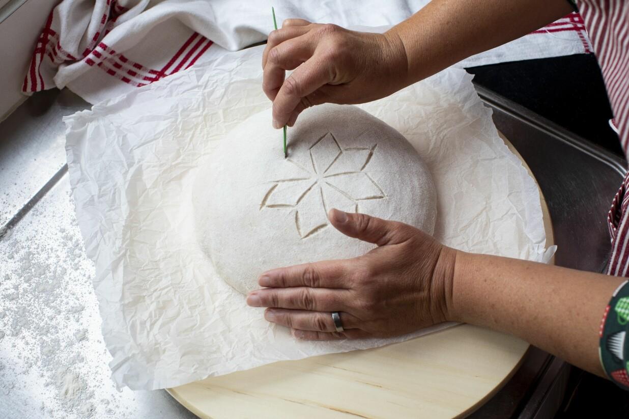 Lisa Södergren snittar stjärnspetsar i sitt surdegsbröd.