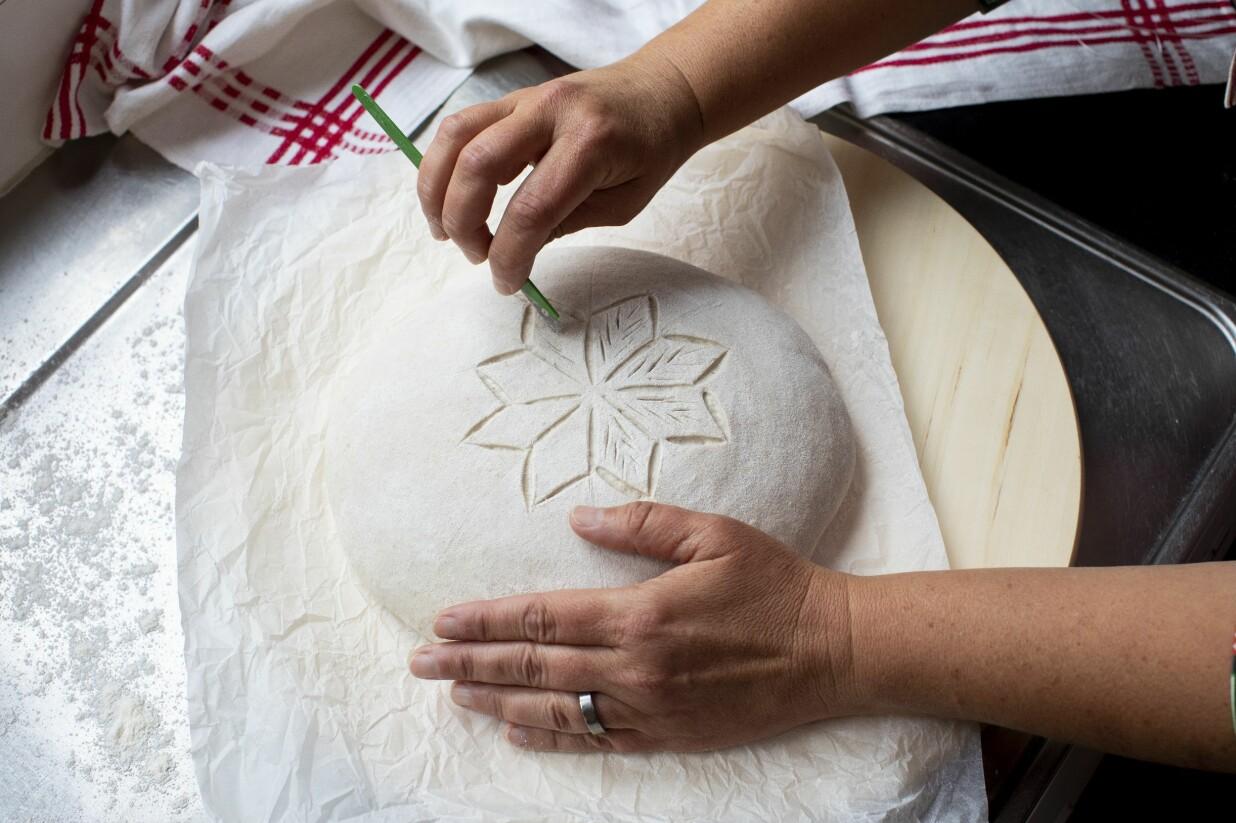 Lisa Södergren dekorerar sin stjärna på surdegsbrödet.