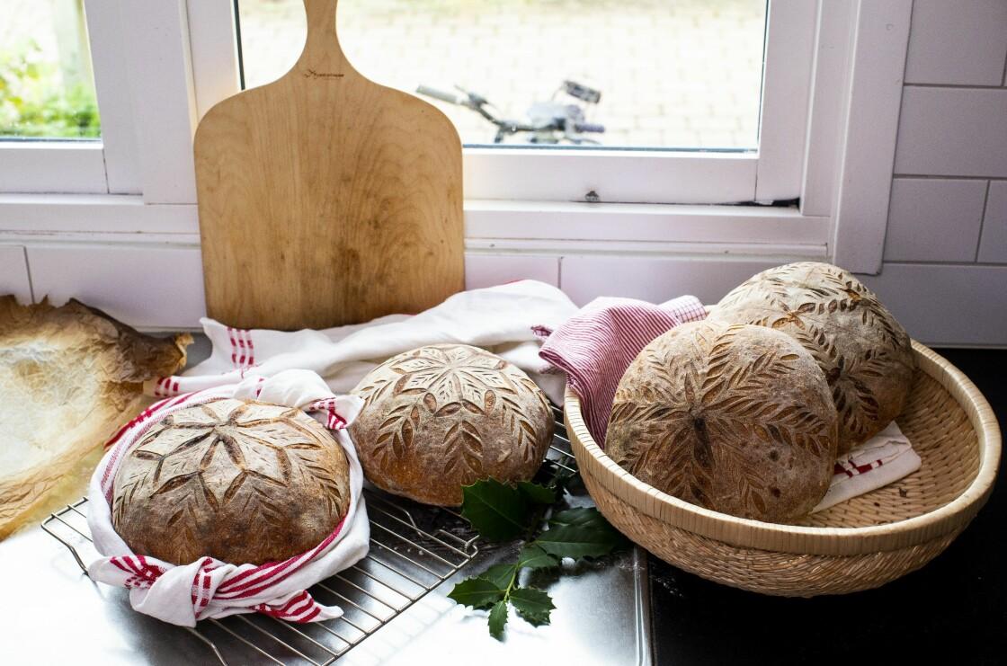 Snittade och bakade surdegsbröd ligger vackert upplagda i ett kök.