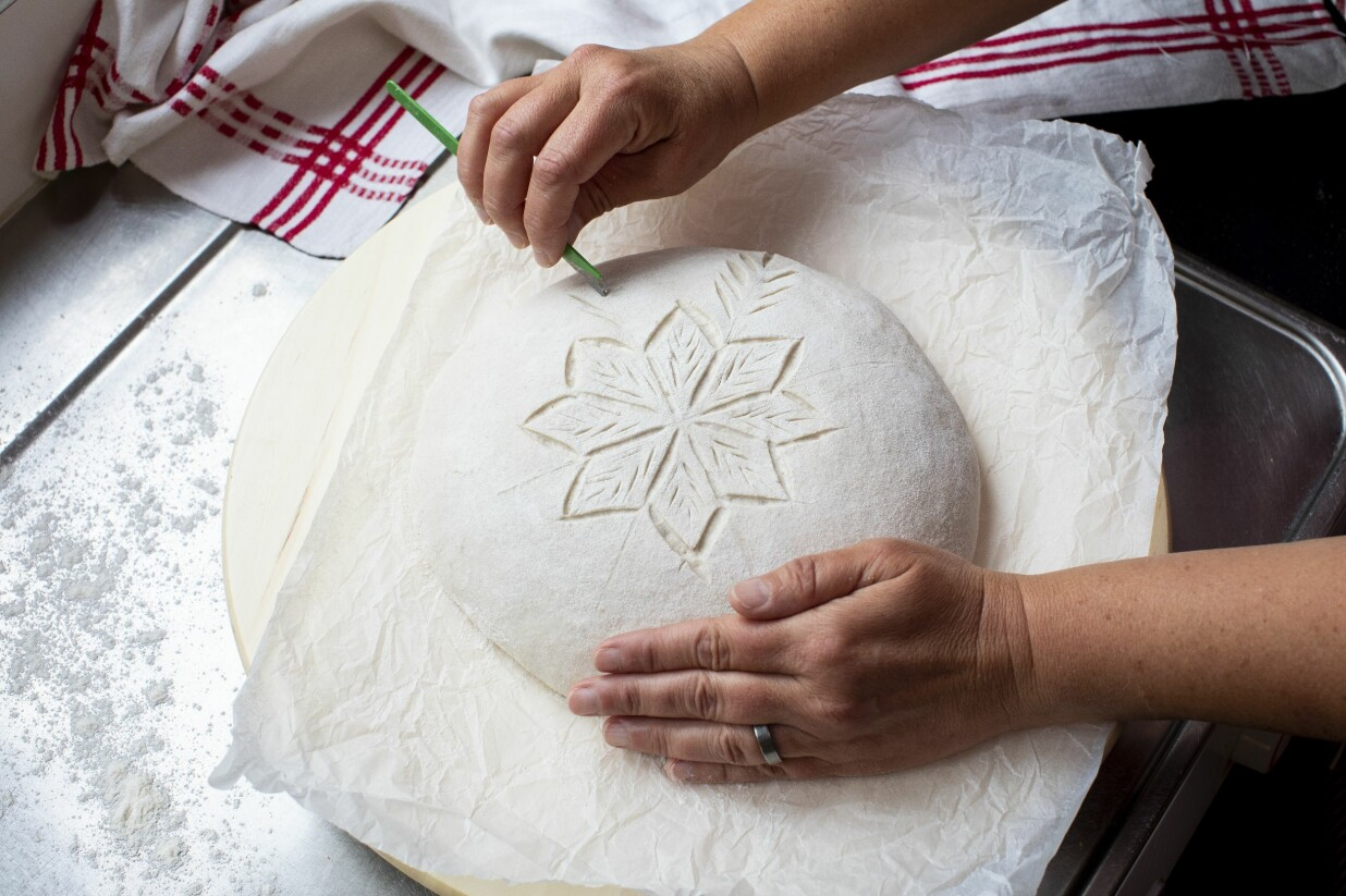 Lisa Södergren snittar det sista mönstret i sitt surdegsbröd.