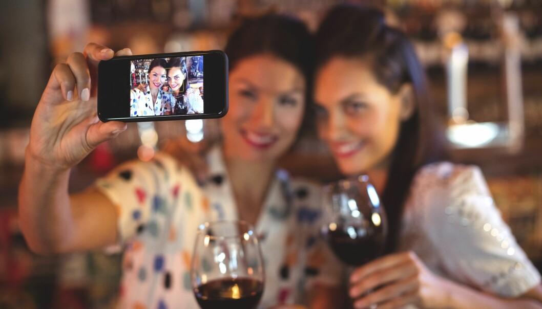 Två leende kvinnor i en soffa en bild på sig själva med mobilen