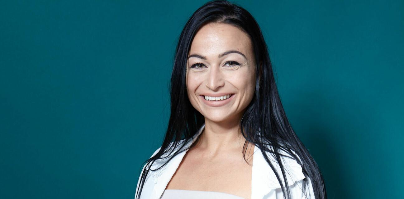 Sofia Sundqvist står vänd mot kameran med ett leende. På sig har hon en vit blus och svarta byxor.