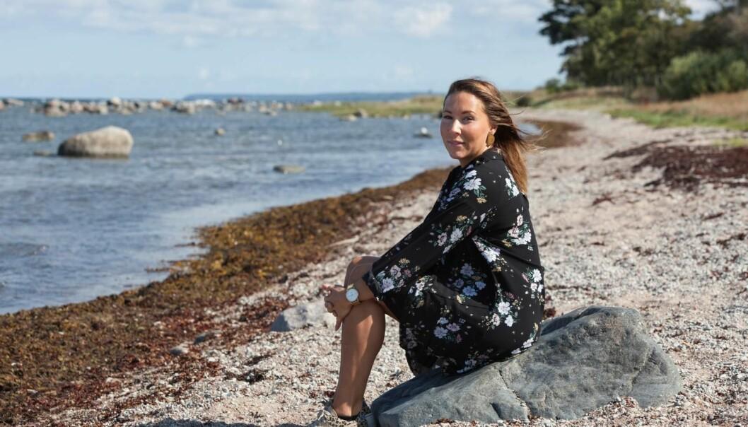 Sofie sitter på en sten på stranden.