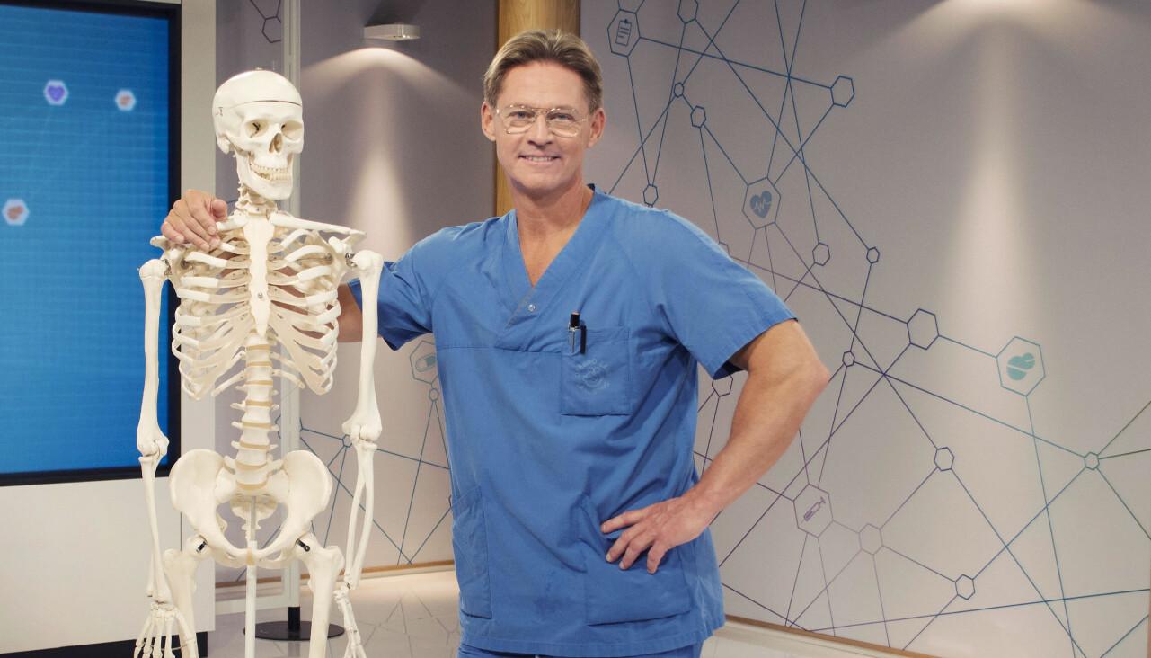 Soldoktorn Mikael Sandström poserar med ett skelett.