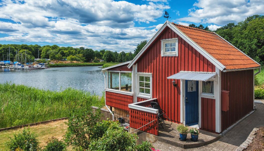 Rött litet sött trähus, med idylliskt läge alldeles vid vattnet och en hamn.