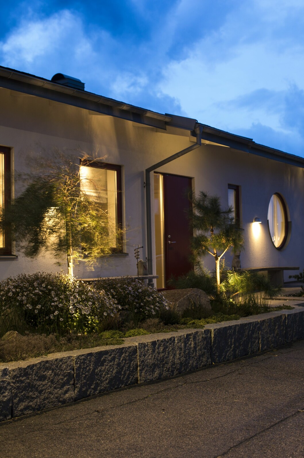 Trädgården har fått belysning i alla ändar – här syns framsidan av huset som bjuder in med lampor längs med väggarna.